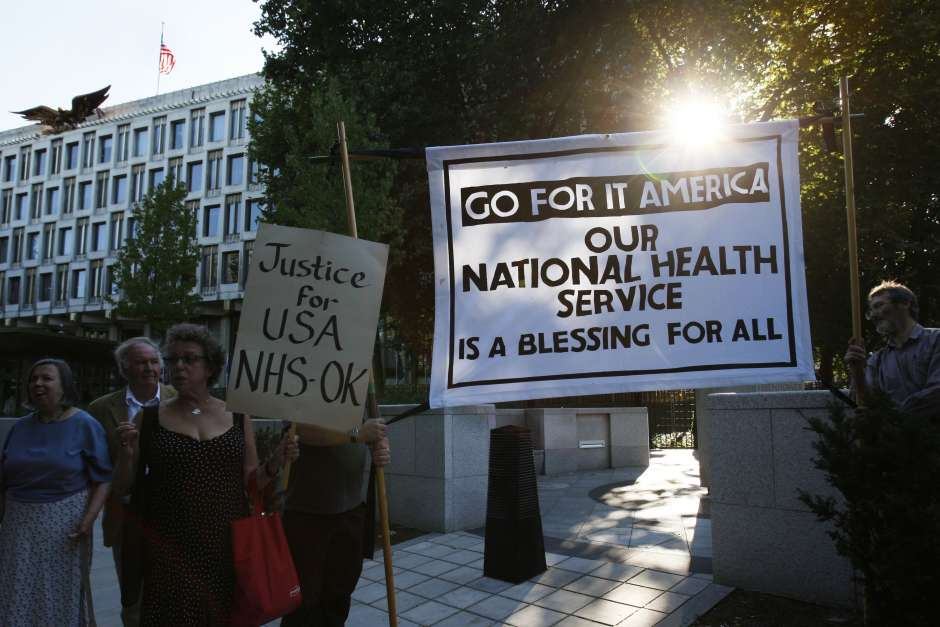 Supporters of Britain's National Health Service hold a banner reading 'Go for it America our National Health Service is a blessing for all' in a demonstration outside the U.S. Embassy in London, during August, 2009./ Sang Tan/AP