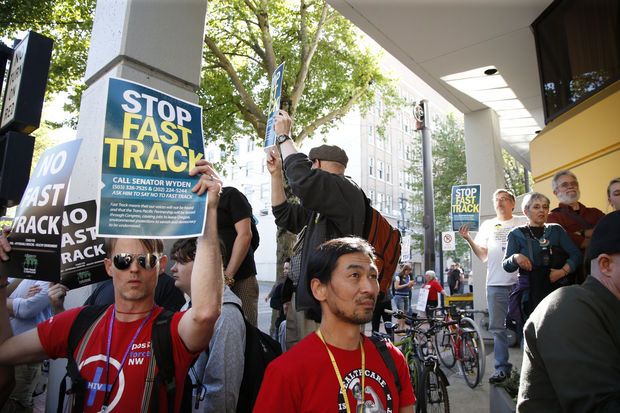 Hyung Nam, center, at rally against Fast Track, May 7, 2015 (photo by The Oregonian)