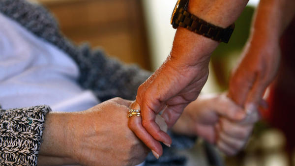 A registered nurse checks the strength of a patient's grip while performing a home visit in Denver, Colo. In 2009. (John Moore / Getty Images)
