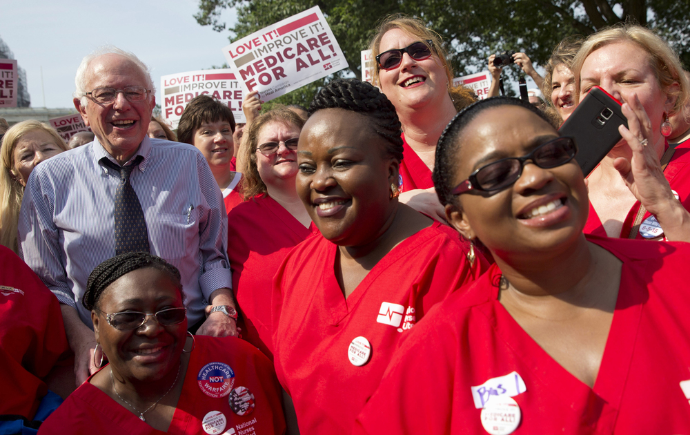 Democratic presidential candidate Senator Bernie Sanders, left, poses with a group of nurses after speaking at a rally on the 50th anniversary of Medicare and Medicaid on Capitol Hill. (AP Photo/Jacquelyn Martin)