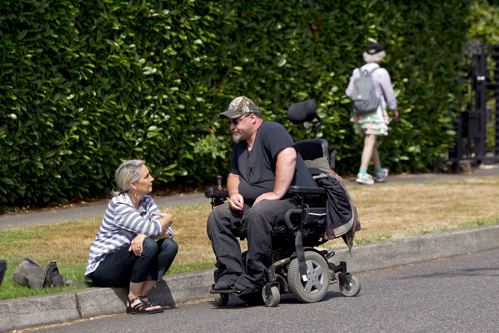 Lisa Pearlstein, a community outreach worker for CareOregon, during a neighborhood visit with her client, Jared Irvin, in Milwaukie, Ore. (Steven Gibbons/For the Post-Gazette)