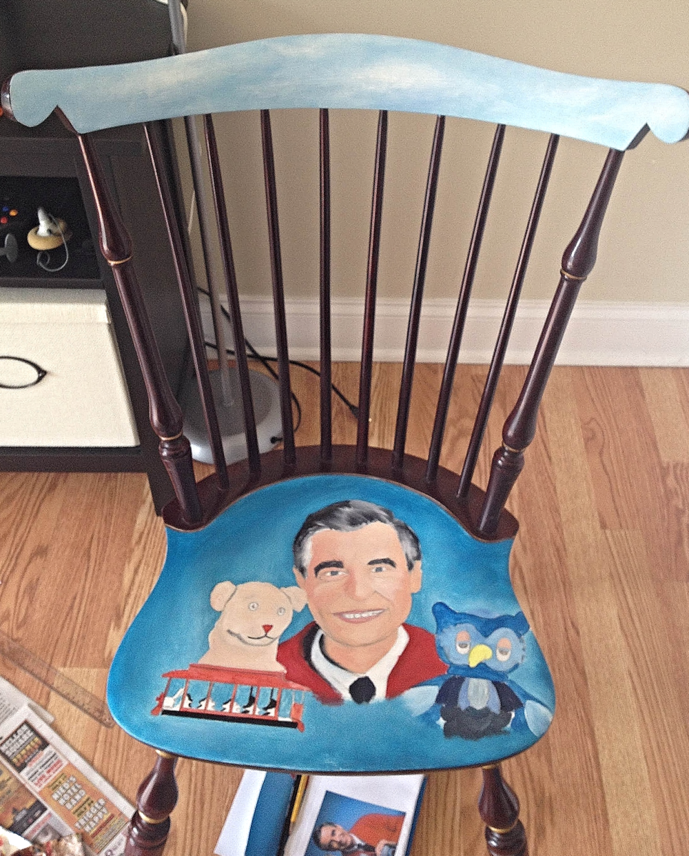 "Photo 2. Luckily after I put a layer of oil paint and color block the entire chair, the chairs finish does not bleed through. I also  painted a quick blue sky with clouds on the top of the chair where I later write the famous Fred Rogers quote "" Anyone who does anything to help a child in his life is a hero to me."" I thought that quote was nothing short of perfect for the theme of ""The Cradle Will Rock"" event and it goes gracefully with the theme of the chair. An absolutely spot on quote in every way that its too fitting. Side note (As you can tell, I was painting the chair in my living room which was completely taken over by paint and brushes for the duration of time)."