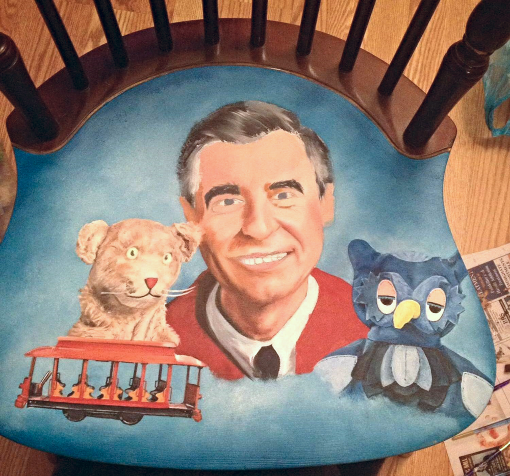 Photo 4. By now my knees having been hurting from sitting and painting on the floor but I've finished Trolley and started working my way onto Mr. Rogers neck and chin. You also might be able to notice when I take a photo of the chair in the natural light and when I was painting with a lamp which gives off a yellow color. This concerned me that my colors would be off from the original picture when I saw it the next morning in the natural light.