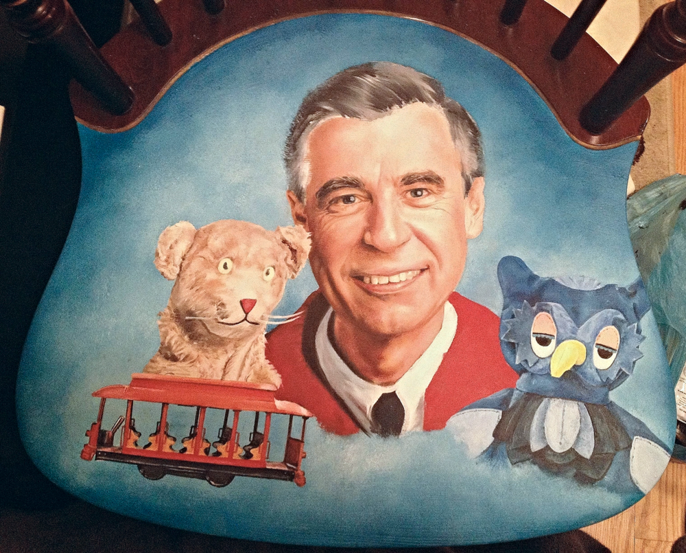 Photo 5. I've finished Mr. Rogers face and I still need to work on his hair and adjust his white shirt collar and sweater. I notice that the design is still pushing  your eye to the right and I need to add more things to the left of the chair to balance everything out for a more eye pleasing composition.