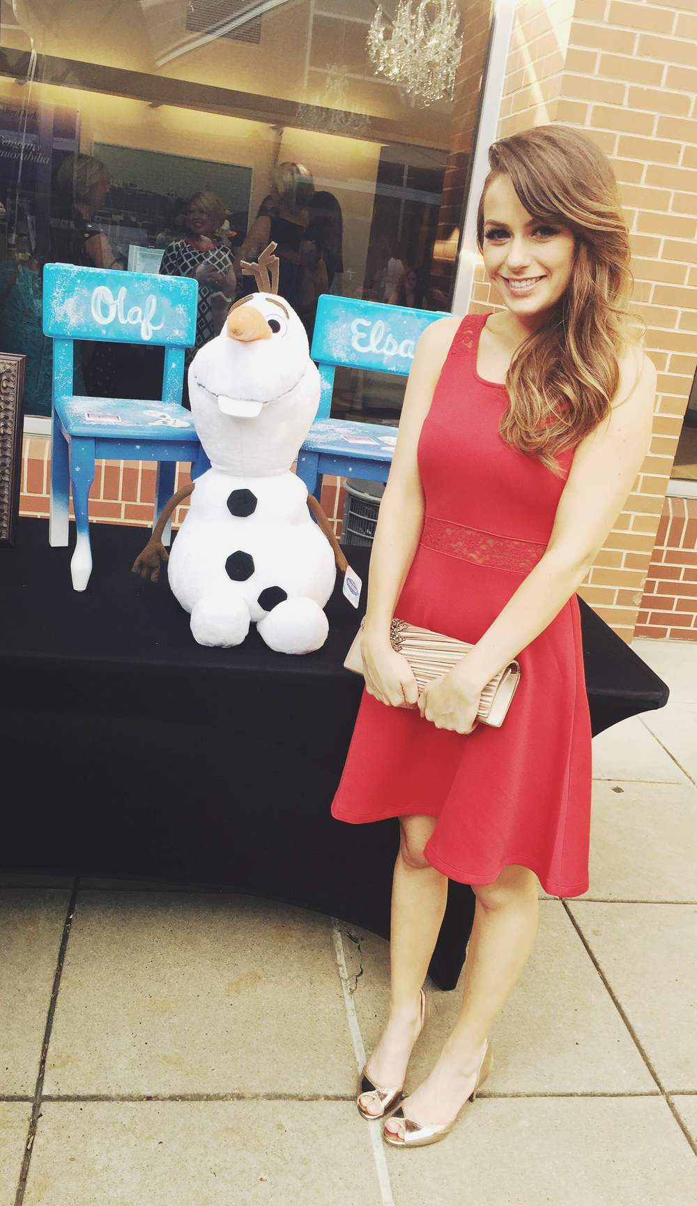 "Kait in front of the "" Frozen"" chairs she painted to be auctioned"