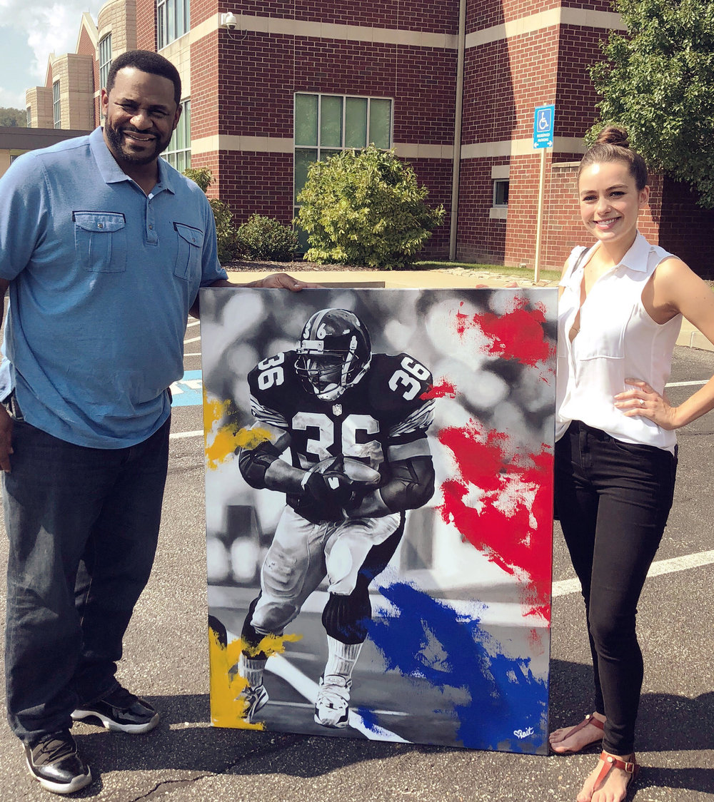 Kait handing off her painting of Jerome Bettis To former Pittsburgh Steeler Jerome Bettis.