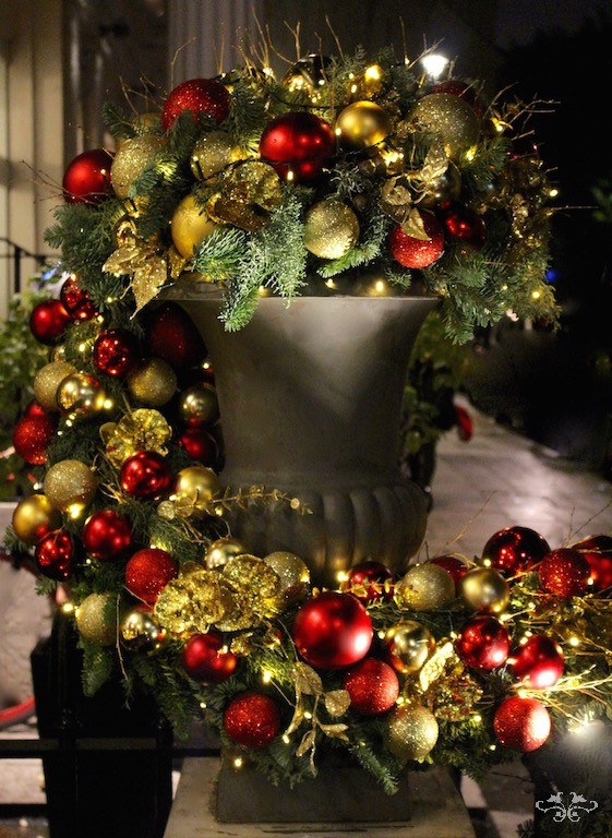 Medici urns ladened with Christmas foliage, baubles and gold Phalaenopsis Orchids. Baroque opulence revival.