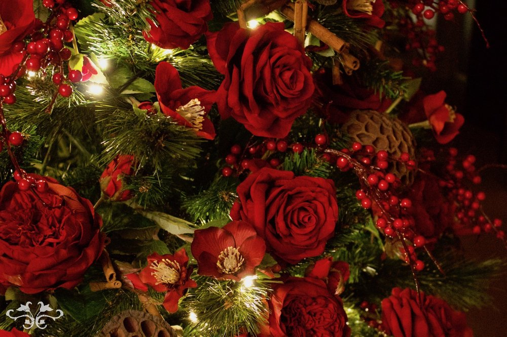 Faux Roses, Hellebores and berries adorn this Neill Strain Floral Couture Christmas Tree.
