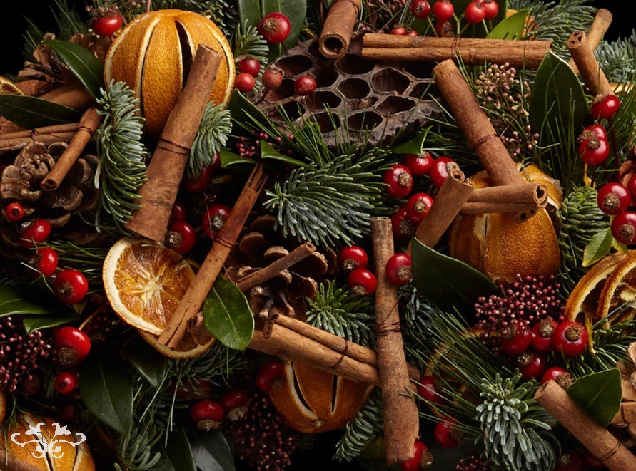 "Traditional Orange, Cinnamon Sticks and berries added to an opulent wreath create a ""touch of organic"" look"