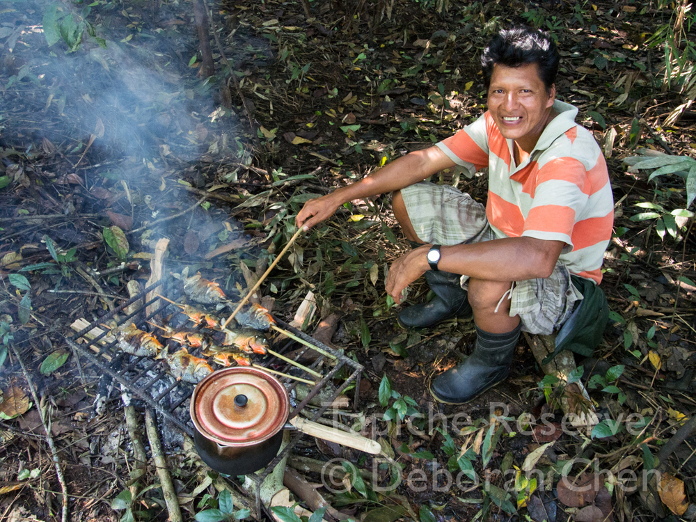Victor tends to our lunch of freshly caught grilled piranhas. Tapiche Reserve, Peru