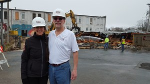 Jeff and Martha Huebner beam with pride as they finally see the first stage of their plan come to fruition. The demolition of the cinder block building in front of what was once the Rouse & Hazard bike factory makes way for the Trefzger's Bakery move to Peoria Heights.