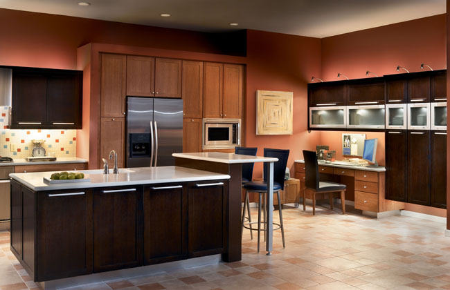 Melrose Quartersawn Oak in Peppercorn and Toffee finishes produces bold lines in this contemporary kitchen.  Toffee cabinets surround the appliances and seem to recede into the wall while the Peppercorn island and dramatic office setup are brought to the fore.