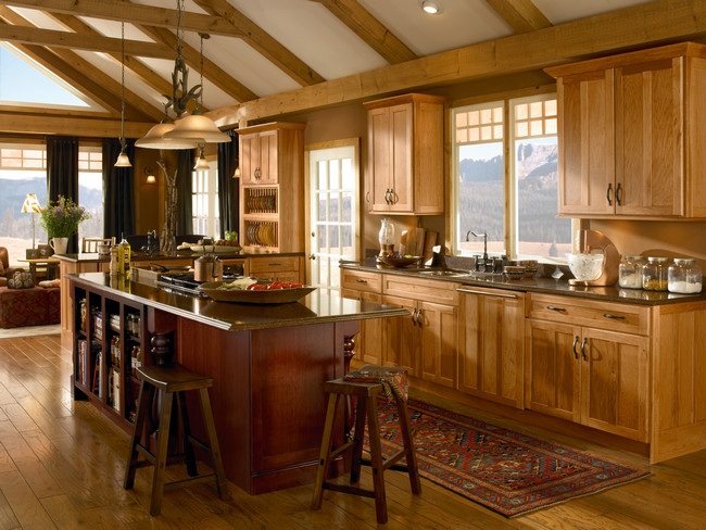 The warm tones of hickory cabinets in Honey Spice are enhanced with an island in Cabernet. The appliance panel maintains the seamless look.