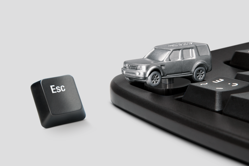 The custom made LR4 Escape Keys are made of plastic resin coated in metallic paint. Making it light and durable for constant office abuse.