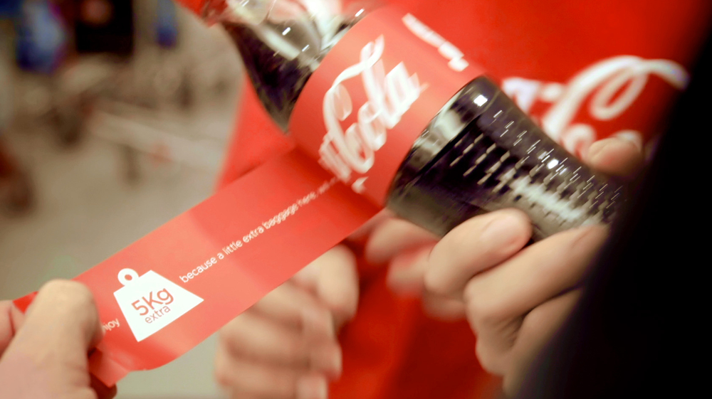 Specially designed Coca-Cola bottle labels were transformed into redeemable excess luggage tags.