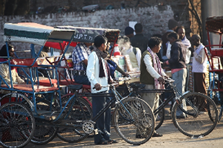 Rickshaw drivers intently waiting                 outside the Delhi train station                          for passengers