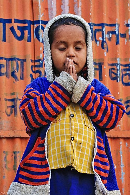 children boy in prayer pose striped sweater Varanasi.jpg