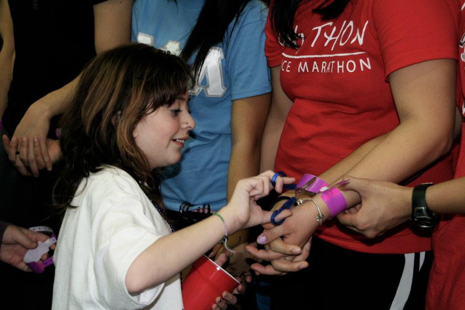 A miracle child cuts off a dancer's hospital bracelet as the 18-hour dance marathon comes to an end. This ceremony is pretty emotional.