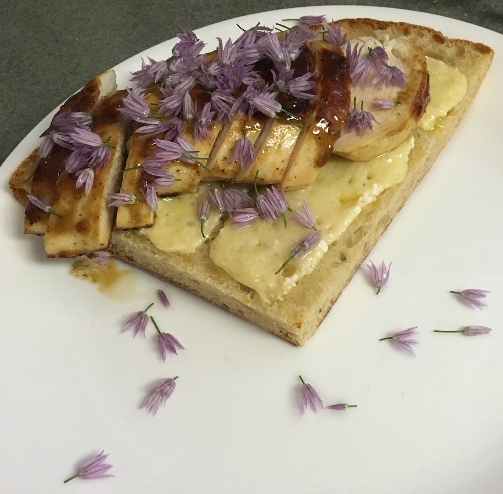 Chive blossoms over chicken with foxhollow more than mustard over sourdough cheese toast