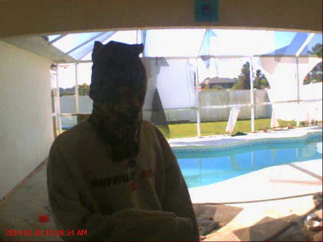 PHOTO:  Surveillance stills of a burglary suspect.  Suspect`s clothing from video: Gray Buffalo Bills sweatshirt, red jeans or pants, black athletic shoes, face covered with a hood / bag with cut outs for eyes, head was completely covered in the video.  The suspect appeared to be using a cell phone while on the rear lanai of the home.  (Photo Courtesy of Cape Coral Police Department)