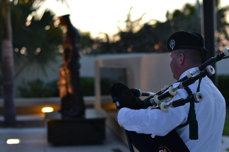 "PHOTO:  Officer Mike Anderson plays the bagpipes.  In the background, ""The Protector"" statue stands illuminated in the courtyard of the Cape Coral Police Department headquarters.  (Photo Courtesy of Cape Coral Police Department)"