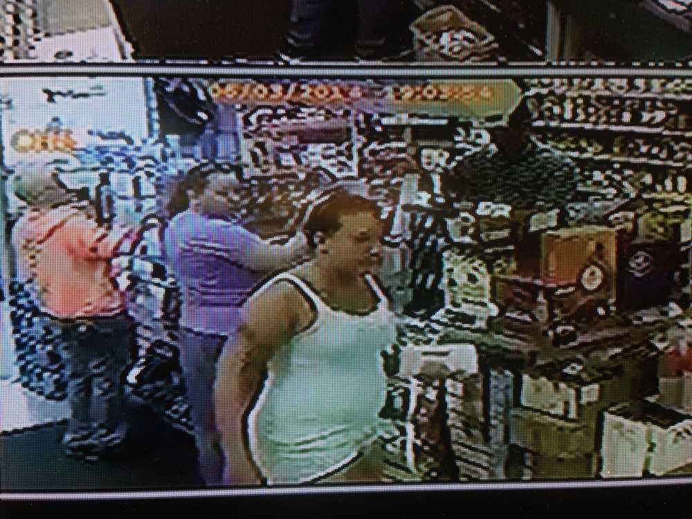 PHOTO:  Stills taken from the liquor store surveillance camera show a W/F, late 30's to early 40's, with dark hair, wearing white shorts and a white tank top.  She appears to have a tattoo on her right arm, below her shoulder. (Photo Courtesy of Cape Coral Police