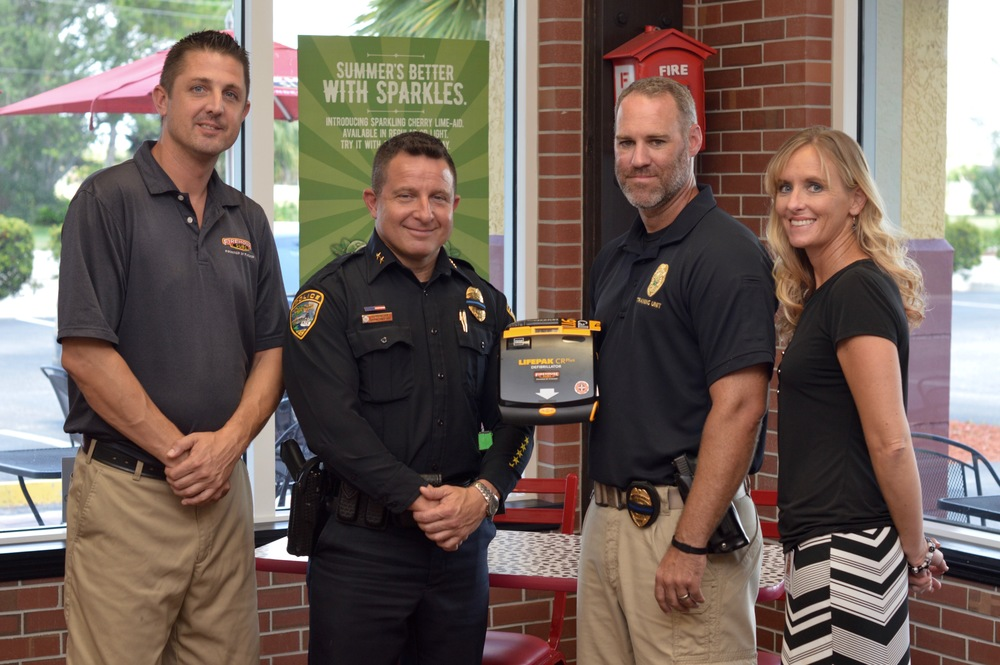 PHOTO:  Interim Chief of Police Dave Newlan, Detective Sergeant Brian Kearney, and Grant Writer Shannon Northorp accept the AED that was awarded by the Firehouse Subs Public Safety Foundation.  The AED was presented to the Cape Coral Police Department on behalf of Firehouse Subs by Store Manager, Dan Redolphy.  (Photo Courtesy of Cape Coral Police Department)