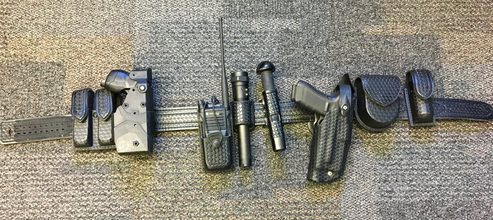 Duty belt L to R: Magazines, Taser, radio, flashlight, baton, firearm, handcuffs, pepper spray.