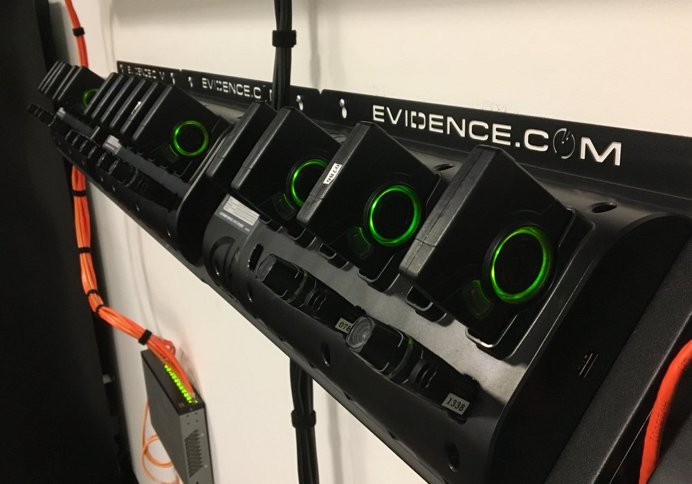 "The ""lipstick"" style Axon Flex camera, with battery packs above, in their docking stations. The station both charges the pack and uploads any video stored. (Photo courtesy of Cape Coral Police Department)"