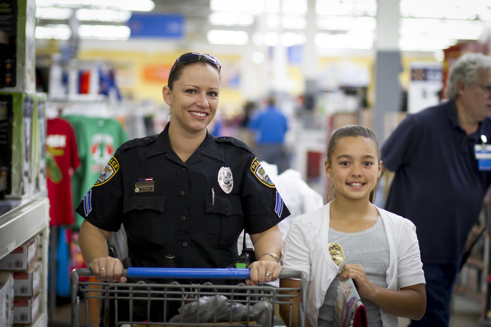 "Cpl. Jen Silko with an excited shopper at past ""Shop With a Cop"" event. Photo courtesy of Portraits by Emma-Louise."