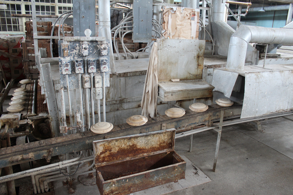 The press molds on a conveyer belt waiting to be dried before being removed from the mold.