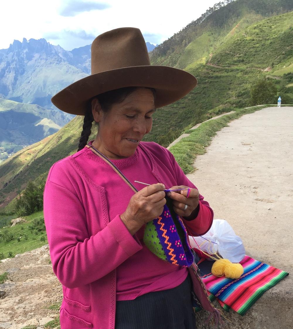 Indianerkvinne som hekler luer for salg. Dette fargerike arbeidet fikk bli med hjem til Norge selv om det ikke var ferdig.