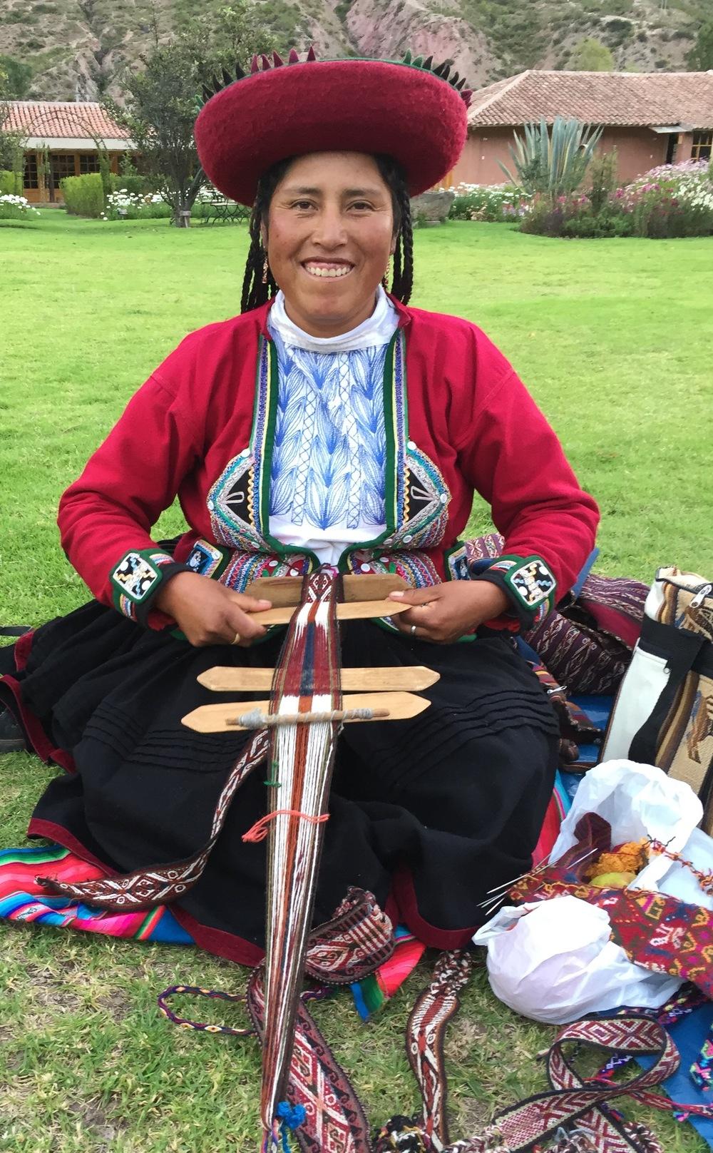 Veven festes i bakken med en liten metallpinne, og så kan man lage de vakreste bånd. Til høyre ligger en påbegynt Chinchero-lue, en såkalt Chullos.