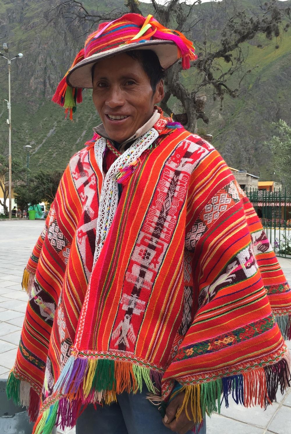 Mann i fargerik poncho og tovet hatt. Inkaenes hellige kondor går igjen blant symbolene som er vevet inn, men også mange andre dyr.