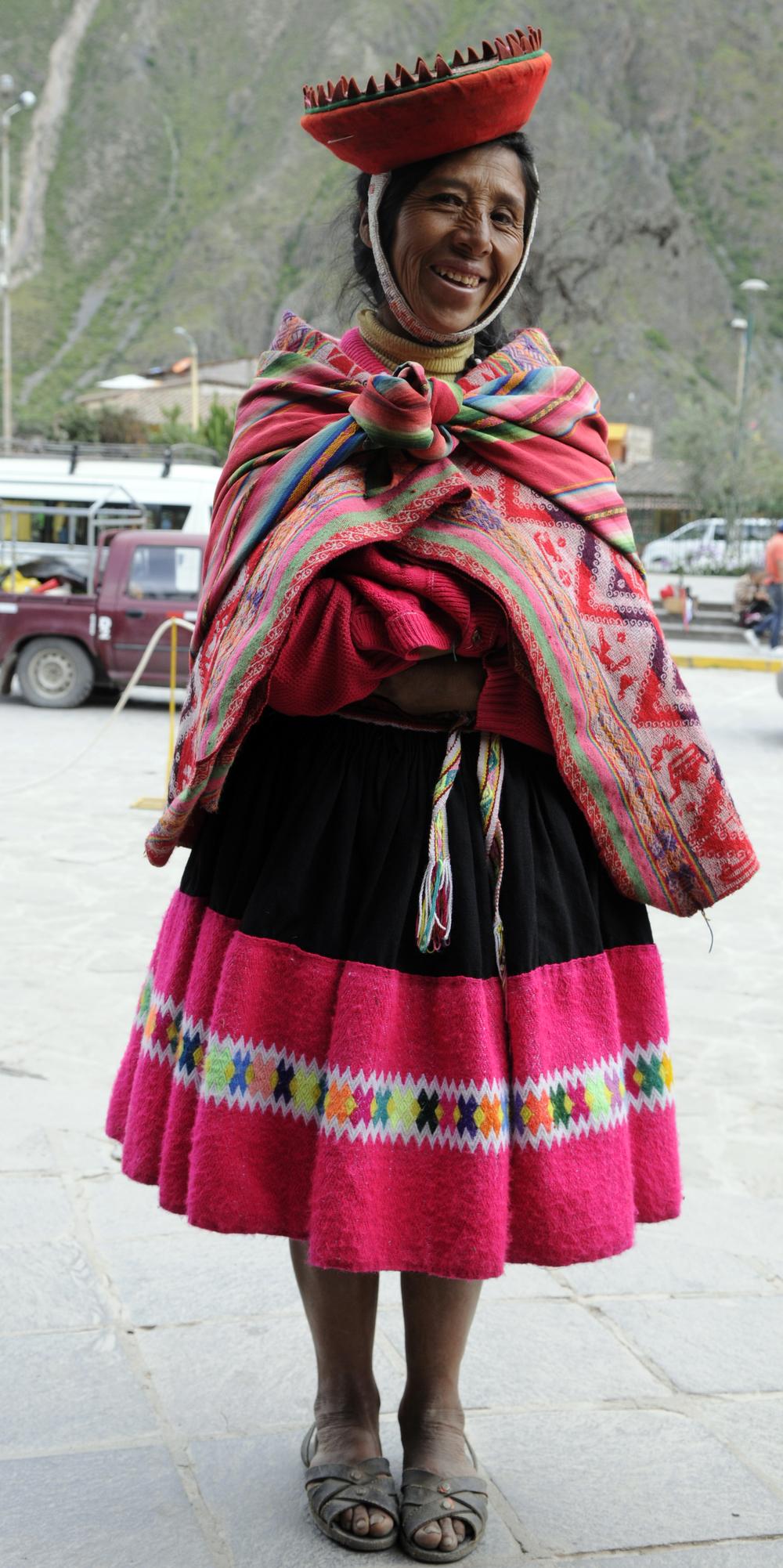 Indianerkvinne på torget i Ollantaytambo. Over skuldrene har hun to tepper, både et mønstervevet og et stripete. I det sistnevnte bærer hun varene sine.