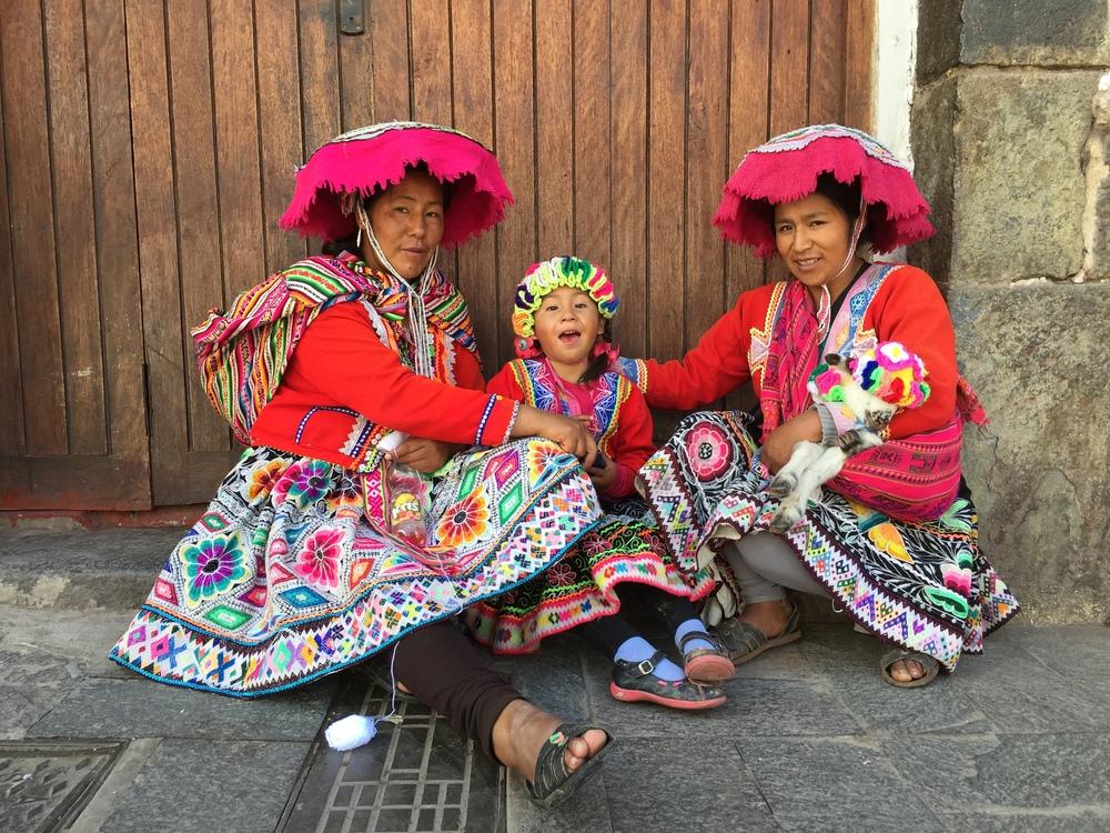 Kvinner som prøver å tjene en slant på å la seg fotografere i lokale drakter.