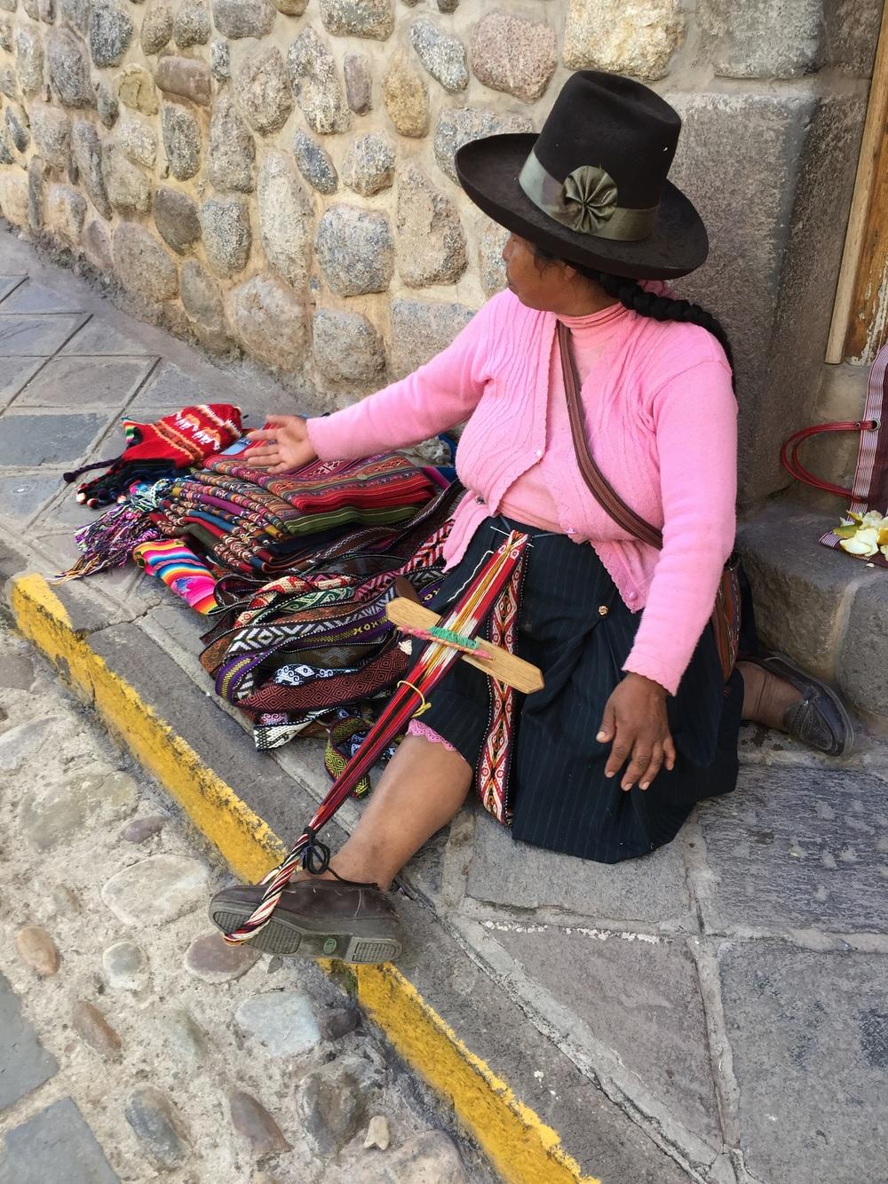 Kvinne som sitter på fortauet med hele varelageret sitt. Renningen har hun festet i foten.