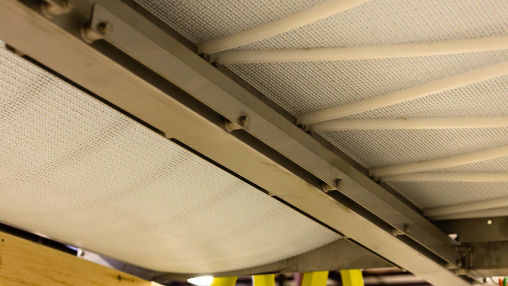 The catenary sag section on the underside of a large modular belt conveyor.