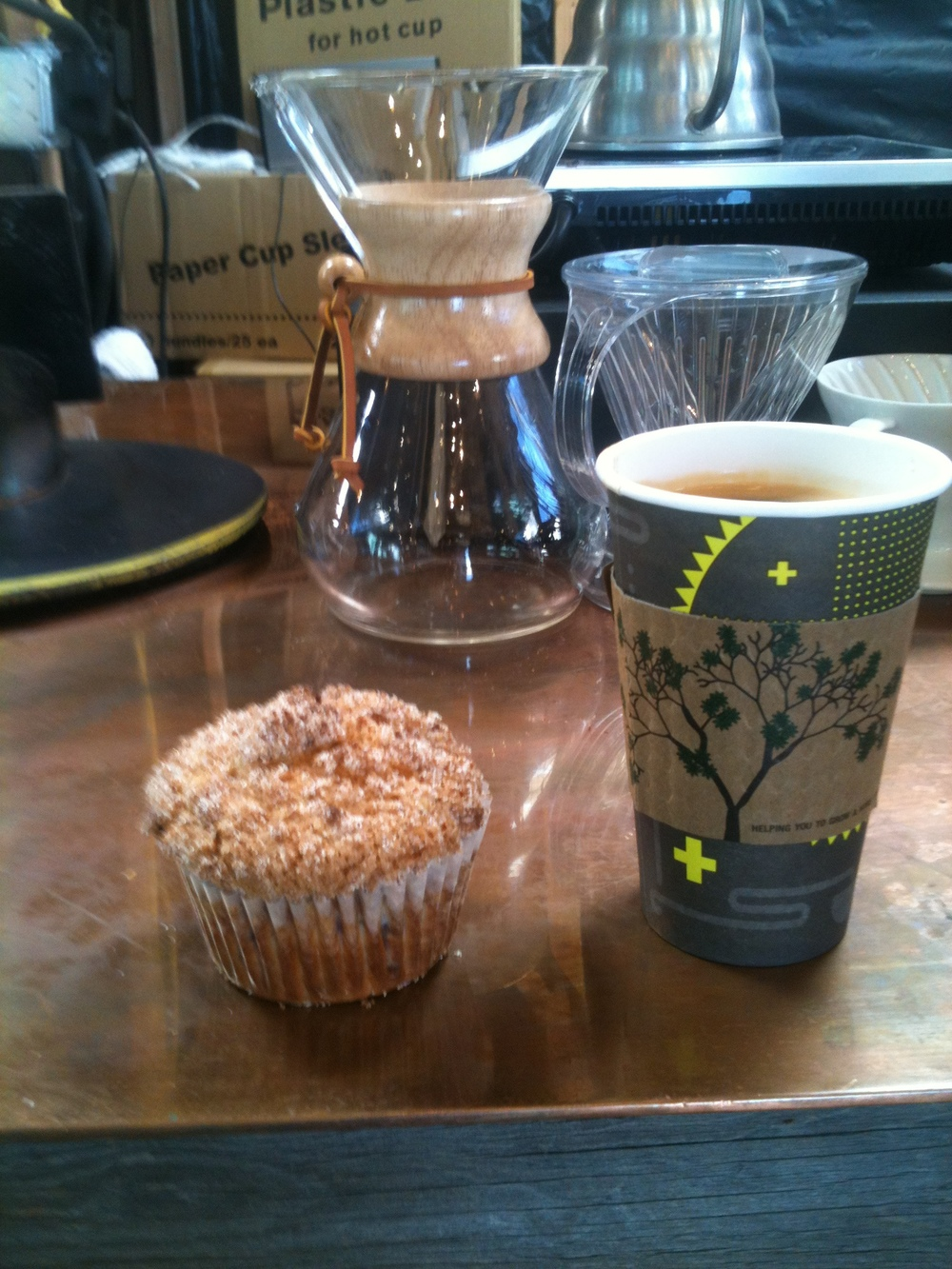 blueberry muffin, 4 shot americano, a caraffe of some sort.