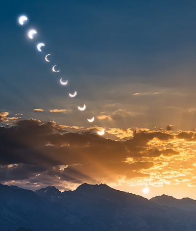 Watch the sun fall as it peeks from behind the moon.  View photograph