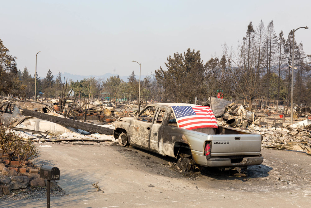 An American flag waves from a partially burned truck among the ruins of hundreds of homes near Coffey Lane in Santa Rosa, CA.