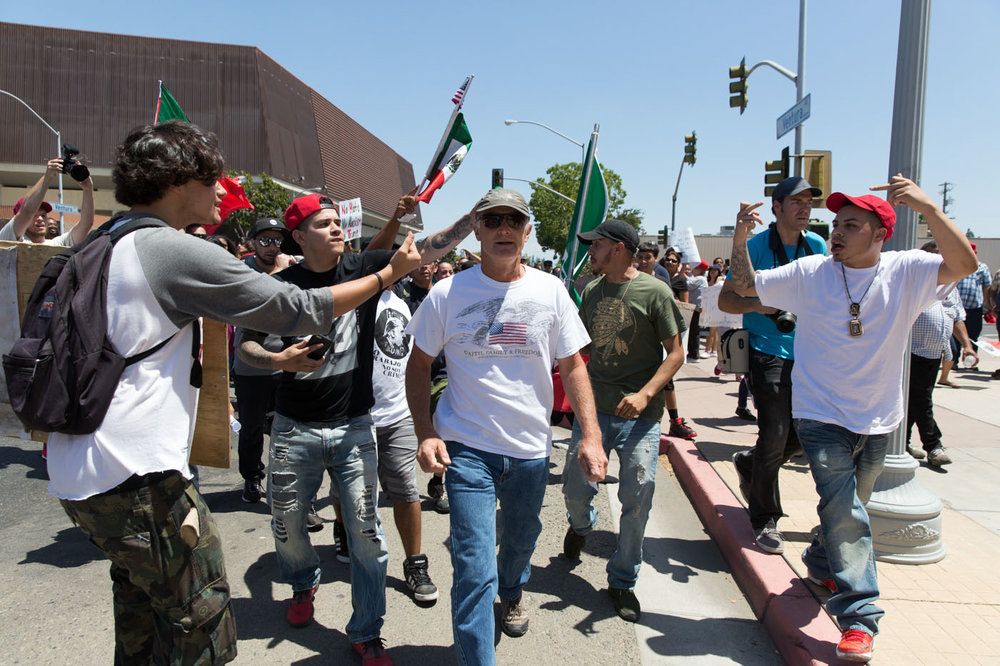 A group of counter-demonstrators taunt a Trump supporter outside of a Trump rally. Fresno, CA. May 2016