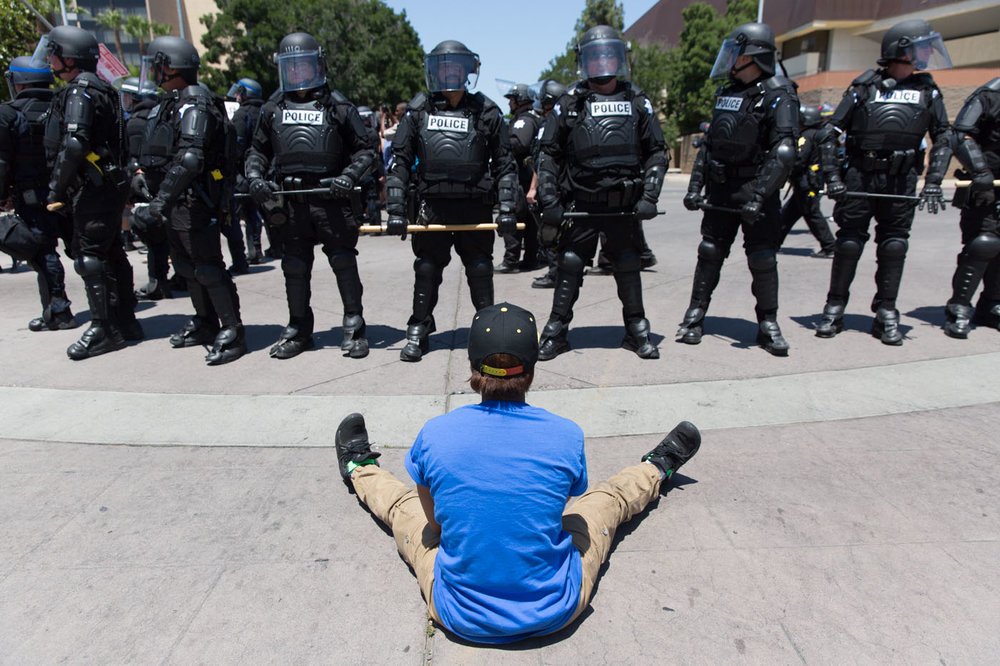 A man sits at a police line outside of a Trump rally in Fresno, CA. May 2016