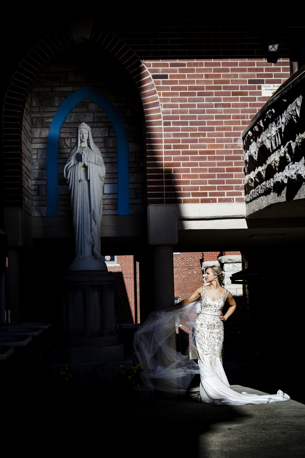 Janna - Jefferson City, MO - Katie set up & took this shot, I was on the walkway to the top right holding a reflector on the Mary statue.  I love the composition of Janna and Mary diagonal and the dark shadows and bright contrast.  We were running out of time when we took this one, about to head into the Church to start the ceremony.  Janna was a sport, willing to take the time to do whatever we thought would look good.