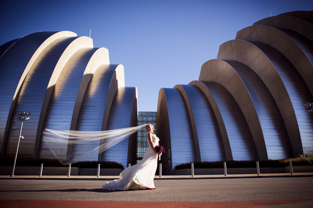 Liza & Nate - Kansas City - Another of Liza.  This shot was taken right before that veil was violently ripped from her head and flew down the street she was standing in.  I was so freaking excited to shoot at this building, I mean, how could you not be, it's ridiculous.  This photo has gotten a lot of attention, it's a combo that is hard to get wrong wind, sun, beautiful bride, cool building.  You have to love a bride that will get out there in the middle of a road in the howling wind with her veil pulling at her scalp. I also loved this wedding because it was on my birthday and I got to hang out with some really amazing people that I love ANNDD because they played the Mizzou Fight song at their reception.  Who does that?  Amazing.