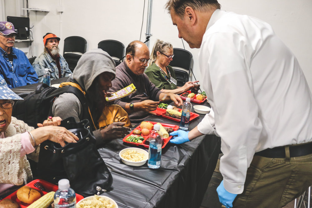 Jack Schwefel, CEO of Cost Plus World Market, serves a meal at the Rescue Mission