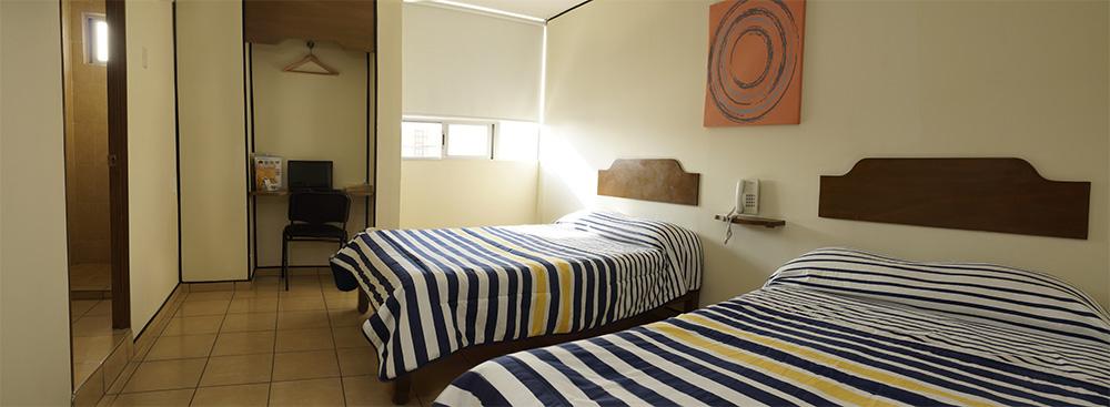 Habitación Doble:  ámplio cuarto con dos camas matrimoniales con esponjoso duvet y doble almohada. Incluye un escritorio ejecutivo, sillón de lectura, chapa electrónica, TV de LCD, WiFi y A/C.