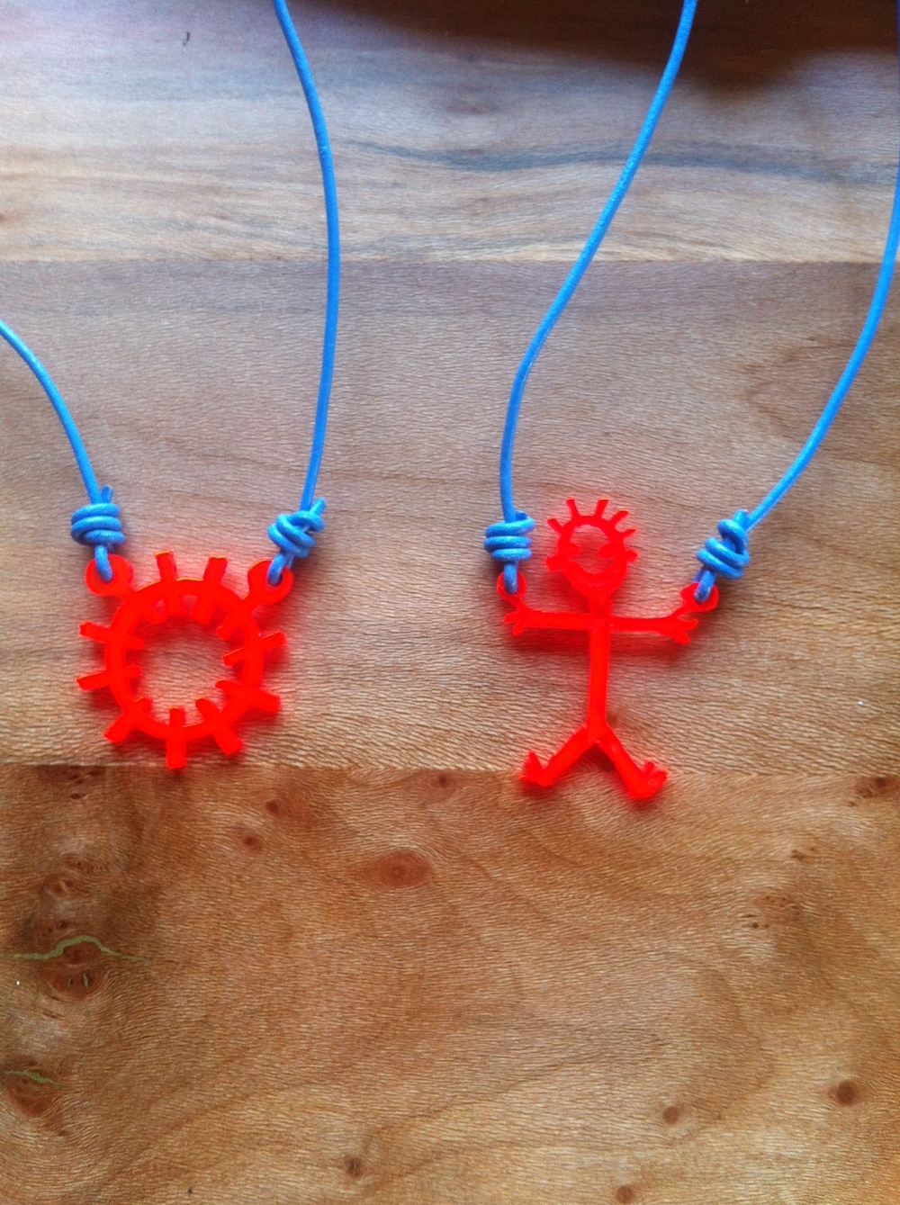 Laser cut necklaces in fluoro orange perspex and blue cord