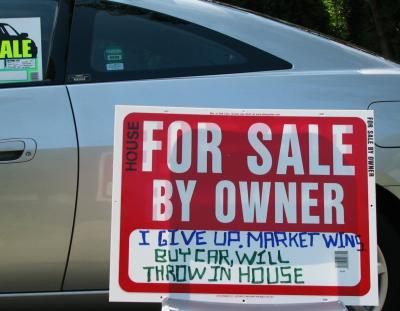 """Pengekrise i USA? På skiltet står det følgende: """"Jeg gir opp, markede vinner. Kjøp bil, du får huset på kjøpet!"""""""