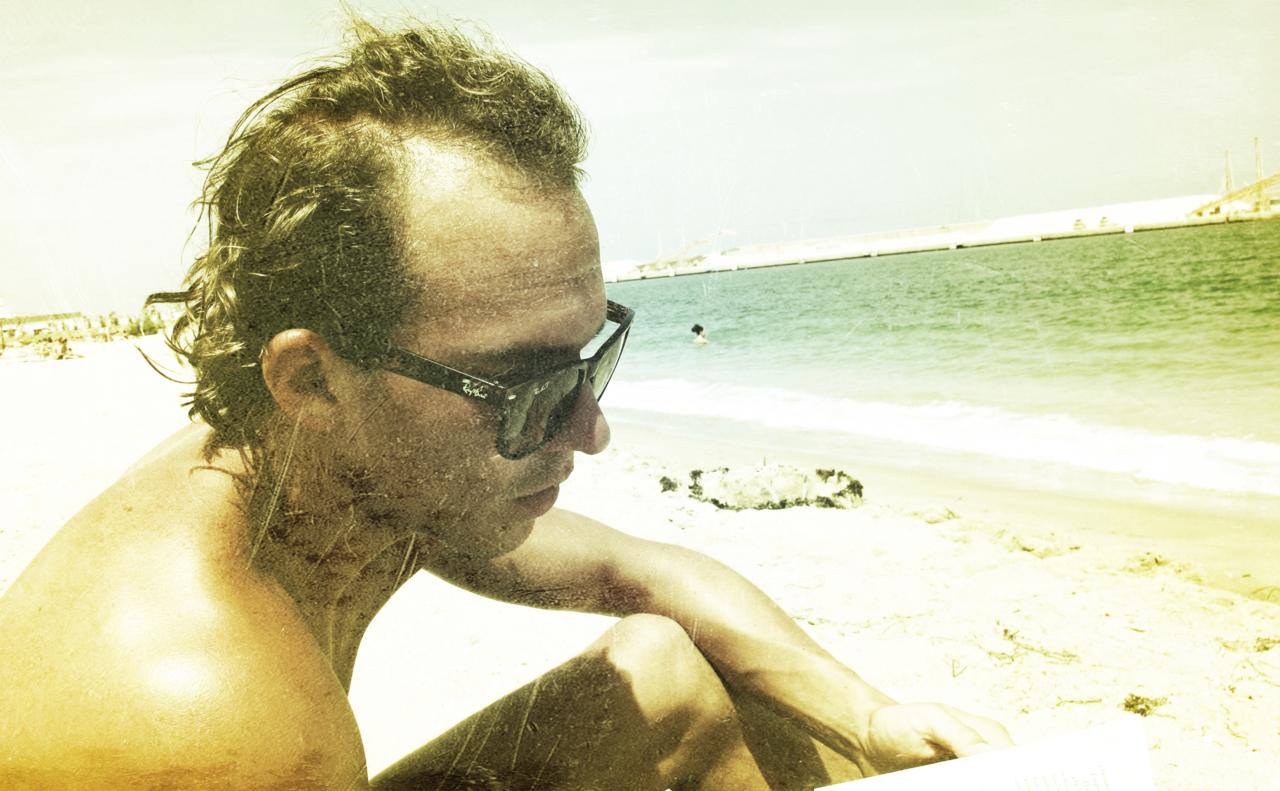 Leser bok på stranda, Spania, Juli 2011.